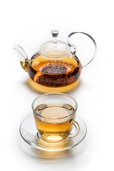 Filiżanka z herbatą i imbryk na białym tle na białej powierzchni