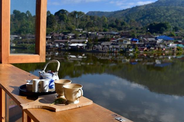 Filiżanka z herbatą i zwalnianie liści herbaty na drewnianym stole i rano w ban rak thai, popularnej atrakcji turystycznej. prowincja mae hong son, północ tajlandii.