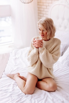 Filiżanka z herbatą. młoda atrakcyjna blond kobieta ubrana w beżowy sweter, trzymająca filiżankę z gorącą herbatą