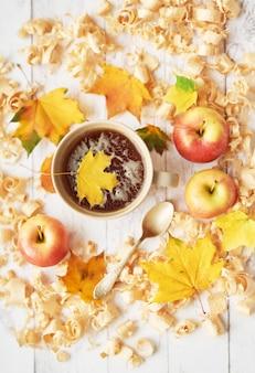 Filiżanka z herbatą na jesieni tle z jabłkami, liśćmi i kwiatami.