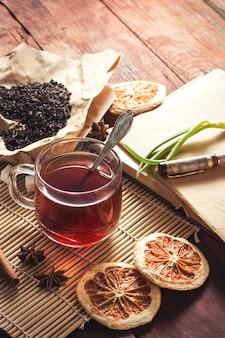 Filiżanka z herbatą, suszonymi liśćmi herbaty na papierze rzemieślniczym, kopertami z cukru i piórem na ciemnym drewnianym stole