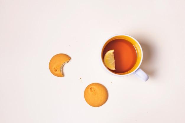 Filiżanka z herbatą z cytryną i ugryzionym ciasteczkiem na beżowym tle.