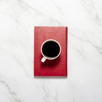 Filiżanka z kawą lub herbatą i czerwoną książką na marmurowym stole. koncepcja śniadanie, edukacja, wiedza, czytanie książek. widok płaski, widok z góry