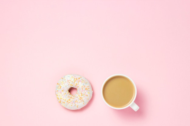 Filiżanka z kawą lub herbatą. świeży smakowity słodki pączek na różowym tle. koncepcja piekarni, świeże wypieki, pyszne śniadanie, fast food, kawiarnia.