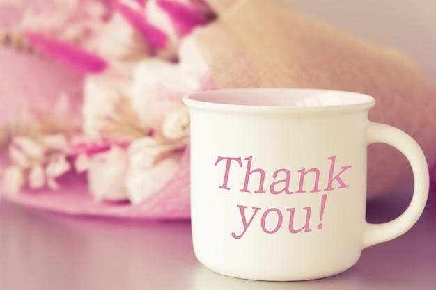Filiżanka z kawą lub herbatą z napisem dziękuję i kwiatami