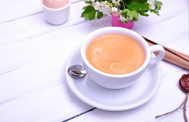 Filiżanka z kawą na białej drewnianej powierzchni