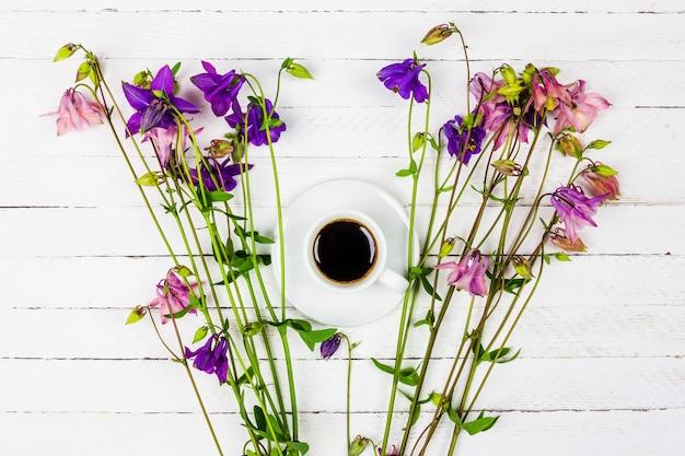 Filiżanka z kawą na białym drewnianym stole z różowymi i niebieskimi kwiatami aquilegii widok z góry