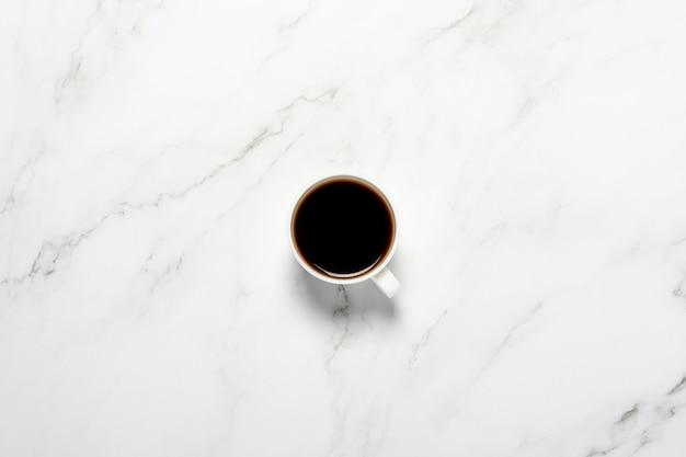 Filiżanka z kawą na marmurowym stole. koncepcja śniadanie, czarna kawa, kawa na noc, bezsenność
