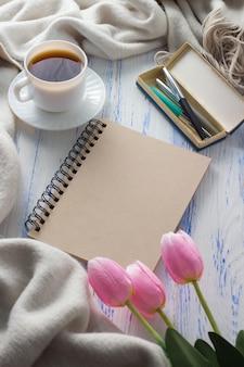 Filiżanka z kawą, notatnik, tulipany, długopisy na białym drewnianym stole. pojęcie wiosny