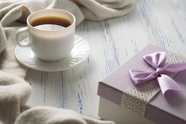 Filiżanka z kawą, prezent na białym drewnianym stole. pojęcie wiosny