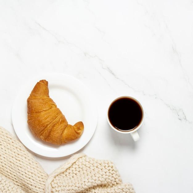 Filiżanka z kawą, rogalik na białym talerzu i dzianinowy szalik na marmurowym stole. koncepcja francuskie śniadanie, przekąska, praca. leżał płasko, widok z góry