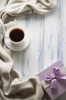 Filiżanka z kawą, szalikiem, prezentem na białym drewnianym stole. pojęcie wiosny