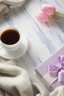 Filiżanka z kawą, szalikiem, prezentem, tulipanami na białym drewnianym stole. pojęcie wiosny