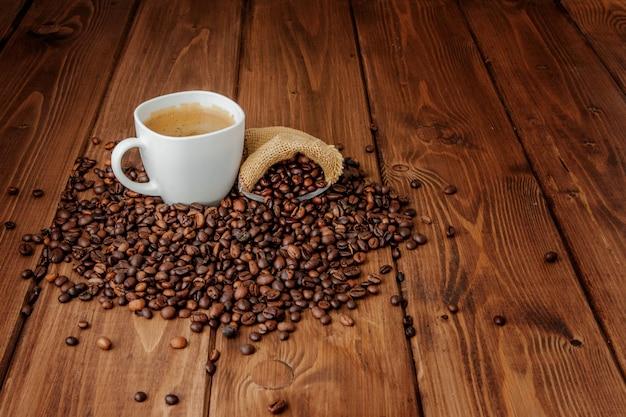 Filiżanka z kawową torbą na drewnianym stole. widok z góry