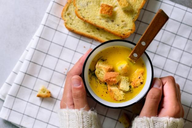 Filiżanka z marchwiową zupą kremową w rękach dziewczyny