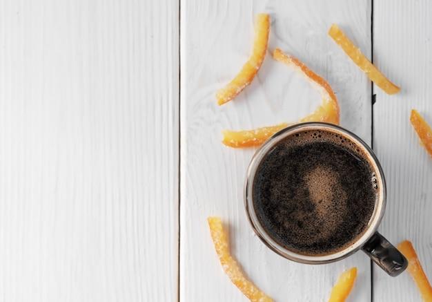 Filiżanka z pachnącym espresso i plasterkami domowych kandyzowanych owoców rozrzuconych na białym drewnianym stole