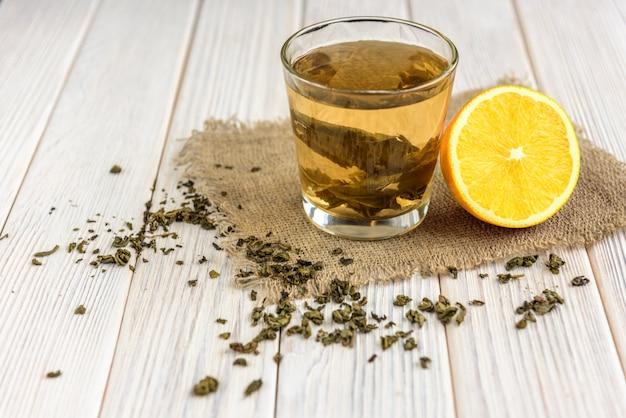 Filiżanka z zieloną herbatą, liśćmi herbaty i cytryną