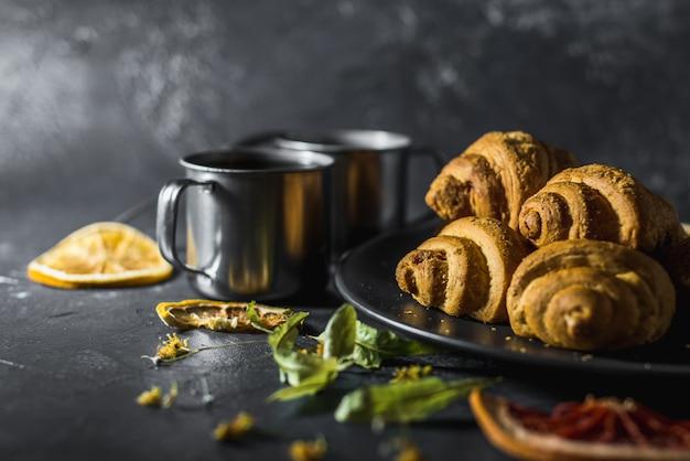 Filiżanka zdrowej herbaty cytrynowej z rogalikami i cytrusami