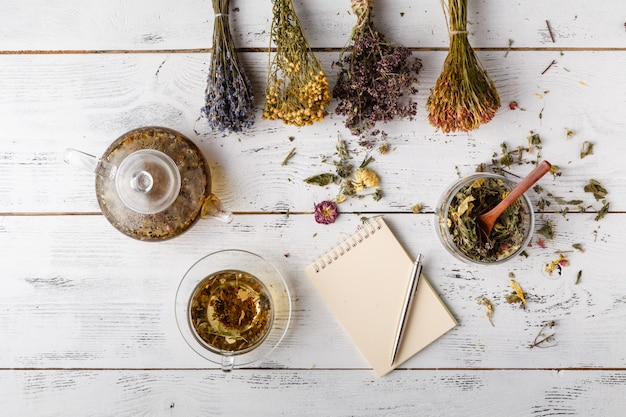 Filiżanka zdrowej herbaty, miodu, ziół leczniczych, asortyment herbat ziołowych i jagód na stole. widok z góry. medycyna ziołowa.