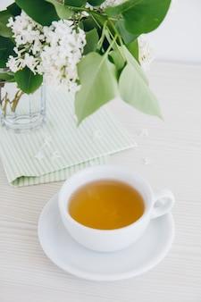 Filiżanka zielona herbata na białym stole