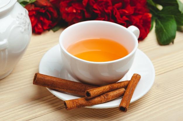 Filiżanka zielona herbata na stole z świeżymi peonia kwiatami