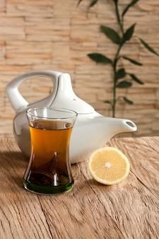 Filiżanka zielonej herbaty i czajniczek na ścianie w tle z kamienną okładziną