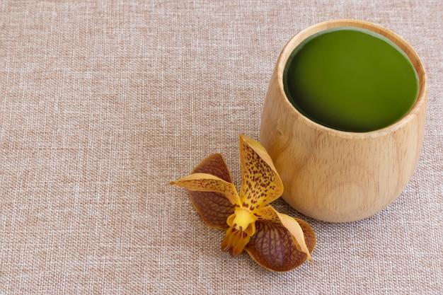 Filiżanka zielonej herbaty jeden tropikalny pomarańczowy żółty orchidea na brązowym tle tkaniny.