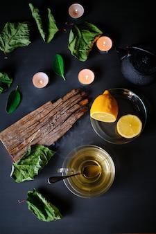 Filiżanka zielonej herbaty, kadzidełko, świece i cytryny na czarnym stole