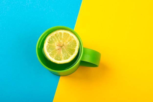 Filiżanka zielonej herbaty z plasterkiem cytryny na żółtej i niebieskiej powierzchni