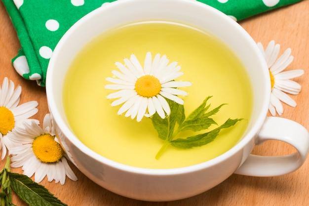 Filiżanka ziołowa herbata z rumiankiem kwitnie na drewnianym stole