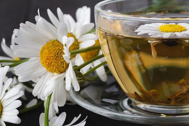 Filiżanka ziołowa rumianek herbata z świeżą stokrotką kwitnie na drewnianym tle. leczenie lekarza i zapobieganie koncepcji odpornościowej