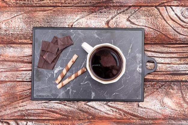 Filiżankę czarnej kawy z czekoladą na starym blacie kuchennym widok z góry