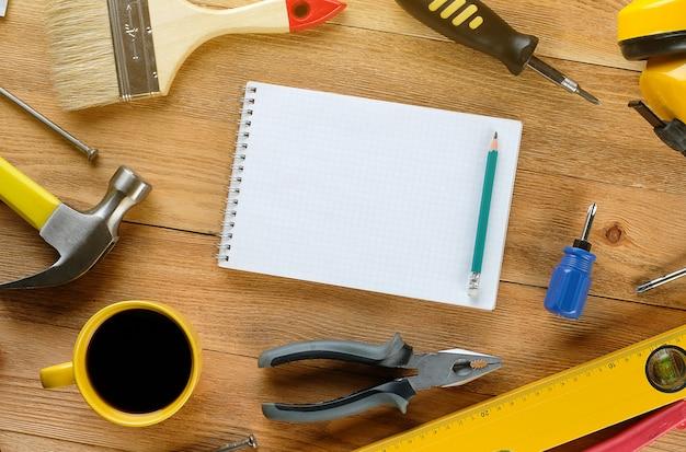 Filiżankę herbaty lub kawy, rysunki i narzędzia do profesjonalnej budowy lub naprawy domu, na drewnianym stole.