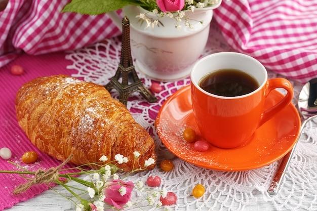 Filiżankę kawy i rogalika zdobi mała wieża eiffla, serwetki, róże i cukierki na białym drewnianym stole