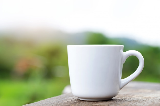 Filiżankę kawy stawia się na stole z naturalną zielenią