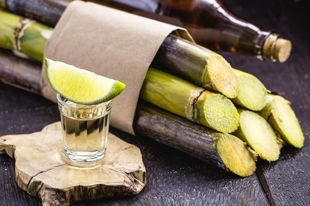 """Filiżanki cachaía z trzciną cukrową w tle, brazylijskiego napoju popularnie zwanego """"pinga"""""""
