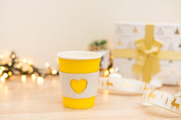 Filiżanki do kawy na wynos na złotym tle światła z prezentami świątecznymi. zdjęcie wysokiej jakości