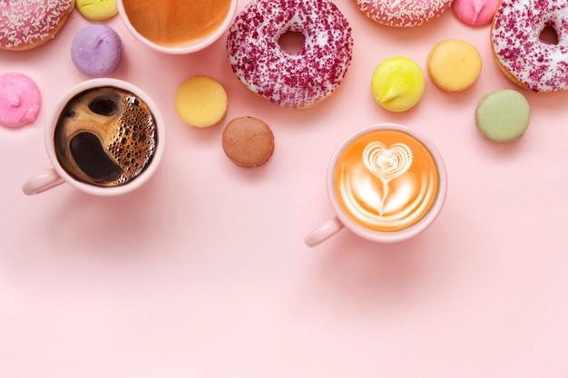 Filiżanki do kawy, pyszne różowe pączki z posypką i kolorowe jasne macarons