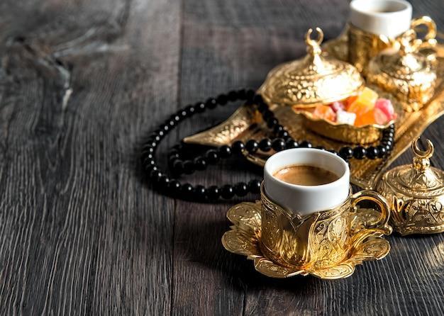 Filiżanki do kawy, rozkosz, złote ozdoby i różaniec. ramadan kareem