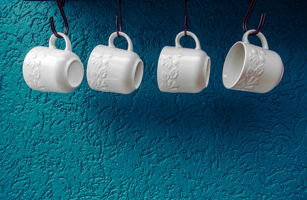 Filiżanki do kawy wiszące na hakach niebieskiej kuchni ściany nowoczesnego wnętrza