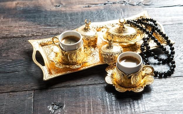 Filiżanki do kawy, złote ozdoby i różaniec. ramadan kareem. koncepcja orientalnej gościnności
