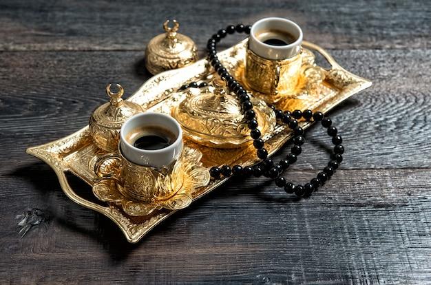 Filiżanki do kawy, złote ozdoby i różaniec. ramadan kareem