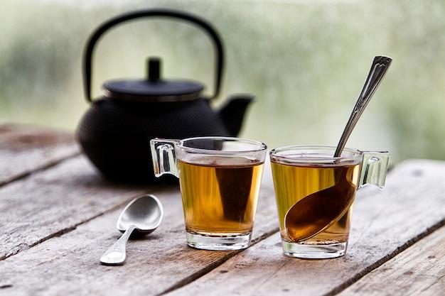 Filiżanki herbaty i czajnik na rustykalnym stole