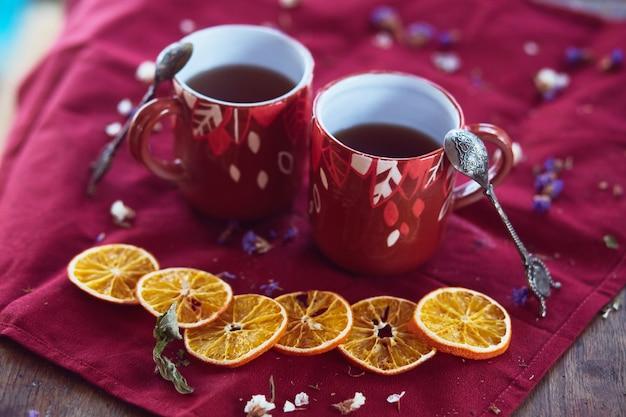 Filiżanki herbaty i kawałki mandarynek stoją na stole