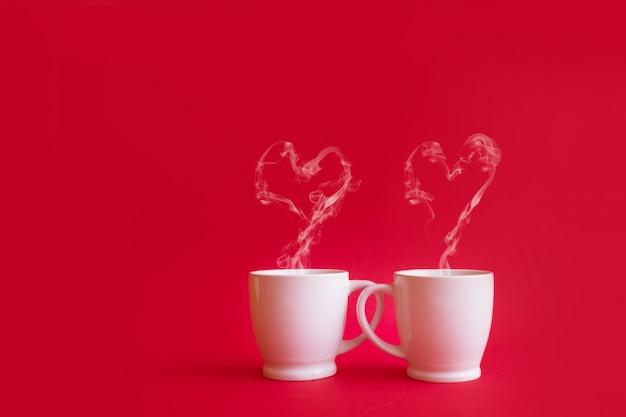 Filiżanki herbaty lub kawy z parą wodną w kształcie dwóch serc na czerwonym tle. walentynki celebracja lub koncepcja miłości. skopiuj miejsce