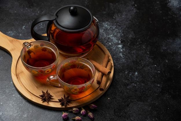 Filiżanki herbaty ziołowej z przyprawami na drewnianej desce.
