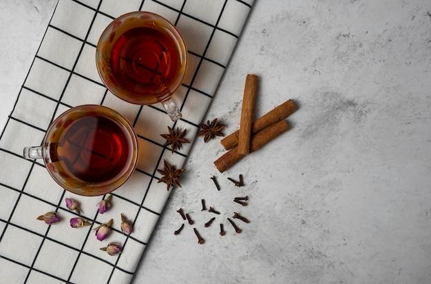 Filiżanki herbaty ziołowej z przyprawami na ręczniku w kratkę.