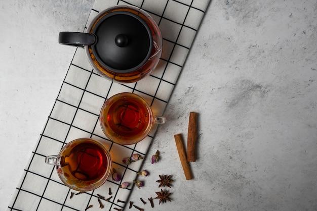 Filiżanki herbaty ziołowej z przyprawami, widok z góry.