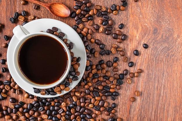 Filiżanki i kawowe fasole na drewnianym stole