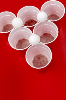 Filiżanki i plastikowa piłka na czerwonym tle. gra pong piwny